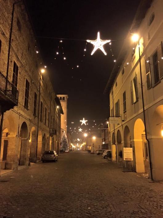 Cherasco, atmosfera natalizia in via Vittorio Emanuele II, in direzione dell'arco di Porta Narzole, con a sinistra la torre del municipio, e a destra lo storico Palazzo Mentone (foto di Bianca Prando)